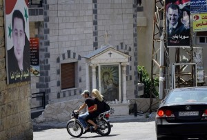 People ride past a Christian shrine and posters of President Bashar al-Assad and a martyr named Dani Adnan al-Hanna in Marmarita in Syria, on August 19, 2013