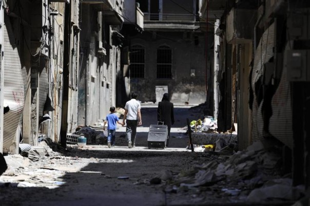 Members of a family walk past damaged buildings as they head to inspect their home in the Wadi Al-Sayeh district at the al-Khalidiyeh area in Homs May 14, 2014. REUTERS/Omar Sanadiki