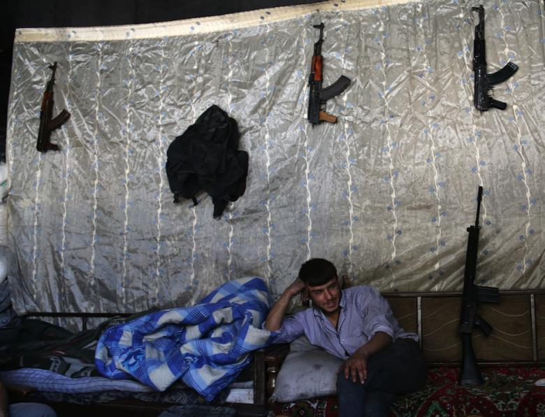 A rebel fighter rests in a safe house in the Bustan al-Basha district of Aleppo on May 19, 2014. (Photo: AFP-AMC/Zein al-Rifai)