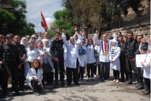 Photo caption: Aleppo Medical Association doctors stand with Syrian soldiers, demanding an end to the western mis-information about Aleppo attacks.