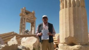 "Tour guide ""Tony"" in front of the ruins of the Temple of Baal blown up by Daesh. He's holding a drawing of the temple as it used to appear. (Photo credit: Jeff Klein)"